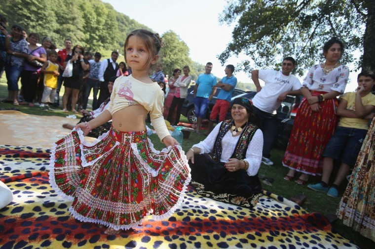 "Kalderash Rom Maria ""Mercedes"" Chiciu, 3, shows off her belly dancing skills as her grandmother Exspertiza Dumitru (sitting) looks on at the field near the Bistrita monastery where thousands of mostly Kalderash Roma have gathered on September 8, 2013 in Bistrita, Romania. Every year thousands of Kalderash Roma from across Romania arrive to visit the nearby monastery to pay tribute to St. Gregory and to gather at the field nearby for a day or more of feasting, dancing, visiting and business dealing. Romania's Roma, many of whom call themselves tsigani, or Gypsies, are divided into different tribes that were once distinctive by their craft. The Kalderash were coppersmiths but today are known for dealing in scrap metal and metal products. Many Kalderash are among Romania's most traditonal and least assimilated Roma and most marry in their teens. (Sean Gallup/Getty Images)"