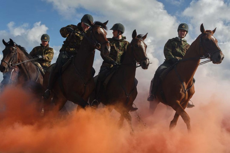 Horsemen ride their horses through colored smoke during a practice session at the beach of Scheveningen on September 16, 2013 in Scheveningen, Netherlands. Some eighty members of the Dutch cavalry practiced for any possible emergency during tomorrow's Prinsjesdag ceremony which marks the opening of the Dutch parliament. (Photo by Jasper Juinen/Getty Images)