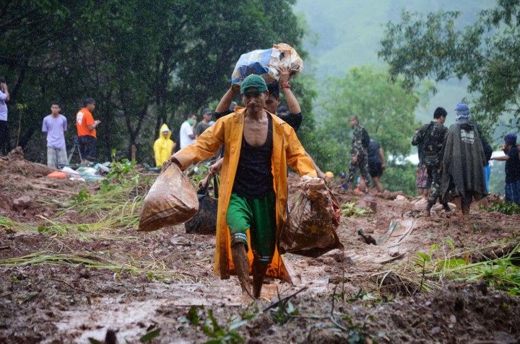Workers and rescue teams clear a landslide area of debris after three days of monsoon rains triggered flash floods and landslides on September 24, 2013 in Castillejos town, Zambales, Philippines. Rural towns north of Manila experienced the worst flooding in recent years, leaving at least 32 dead and hundreds stranded on rooftops, and making roads impassable. (Dondi Tawatao/Getty Images)