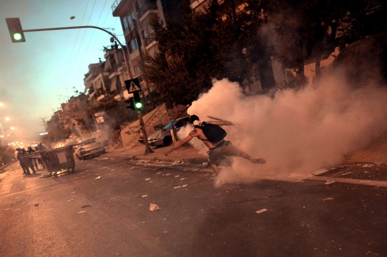 A demonstrator kicks a tear gas can during clashes with riot police in Athens. (ARIS MESSINIS / AFP/Getty Images)