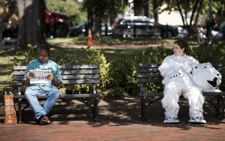 Dressed as a polar bear Megan Gabriel, an activist with the Sierra Club, rests on a bench during a protest in Lafayette Park in Washington, DC. Environmental activists gathered to protest the practice of arctic drilling and pressure the Obama administration to do the same. (BRENDAN SMIALOWSKI / AFP/Getty Images)