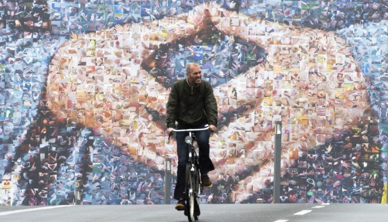 A cyclist rides past a giant election billboard featuring German Chancellor Angela Merkel's hands in a trademark pose in Berlin September 3, 2013, ahead of general elections on September 22. (John MacDougall/AFP/Getty Images)