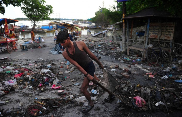 An Indian man clears debris from the banks of the Ganga river as the flood level recedes in Allahabad on September 3, 2013. (Sanjay Kanojia/AFP/Getty Images)