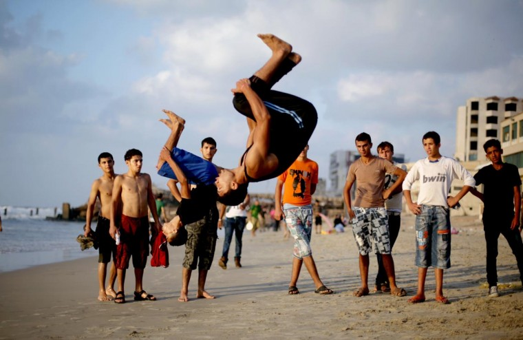 Palestinian youths backflip on the beach in Gaza City on September 4, 2013. (Mohammed Abed/AFP/Getty Images)
