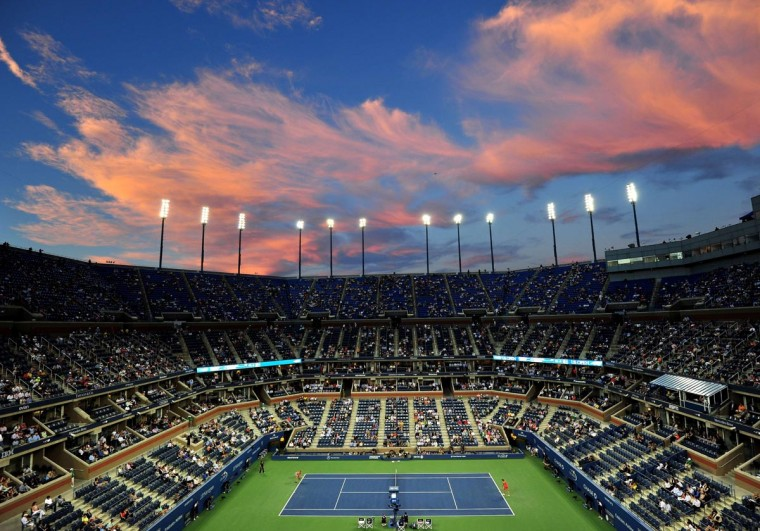 Clouds reflect light from the setting sun over Arthur Ashe Stadium as Victoria Azarenka of Belarus (L) plays Daniela Hantuchova of Slovakia (R) during their 2013 US Open women's singles quarterfinal match at the USTA Billie Jean King National Tennis Center September 4, 2013 in New York. (Stan Honda/AFP/Getty Images)