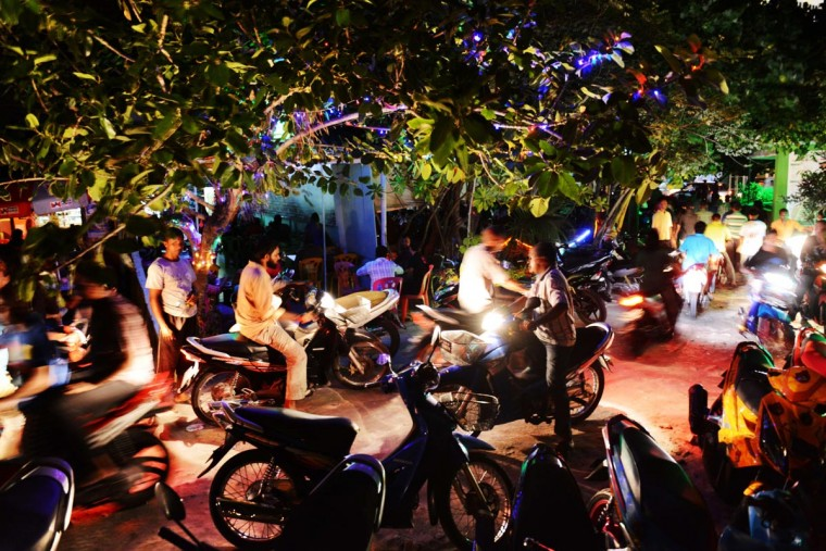 Residents of Male, the capital of Maldives, use mopeds to drive past a popular night spot of the city on September 4, 2013. The island city is home to about 120,000 and mopeds are the most popular mode of transportation in the streets of this very small, crowded city. (Roberto Schmidt/AFP/Getty Images)