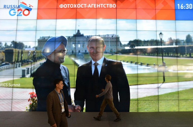 Journalists walk past a screen in the media center showing Russia's President Vladimir Putin and Indian Prime Minister Manmohan Singh during the G20 summit on September 5, 2013 in Saint Petersburg. Russia hosts the G20 summit hoping to push forward an agenda to stimulate growth but with world leaders distracted by divisions on the prospect of US-led military action in Syria. (Kirill Kudryavtsev/AFP/Getty Images)