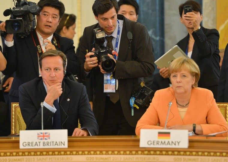Germanys Chancellor Angela Merkel (R) and with British Prime Minister David Cameron (L) wait before a working meeting of the G20 summit of heads of state and government, heads of invited states and international organizations in Saint Petersburg on September 5, 2013. Russia hosts the G20 summit hoping to push forward an agenda to stimulate growth but with world leaders distracted by divisions on the prospect of US-led military action in Syria. (Vladimir Astapkovich/AFP/Getty Images)