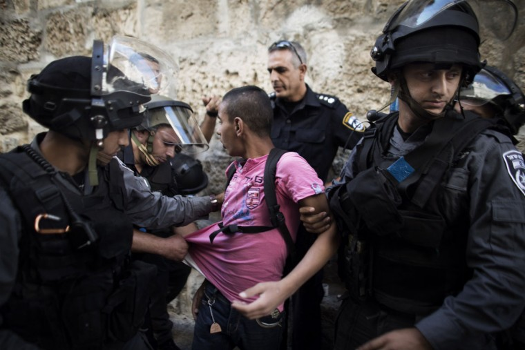 Israeli police detain a Palestinian youth outside the entrance of the al-Aqsa mosque compound in Jerusalem's Old City on September 6, 2013, after clashes between Palestinian stone throwers and Israeli police forces erupted. (Marco Longari/AFP/Getty Images)