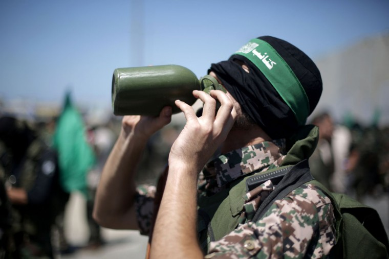 A Palestinian militant drinks water during a march in Beit Lahia in the northern Gaza Strip on September 6, 2013, against peace talks between Israel and the Palestinians, as well as a possible US strike on Syria. (Mohammed Abed/AFP/Getty Images)