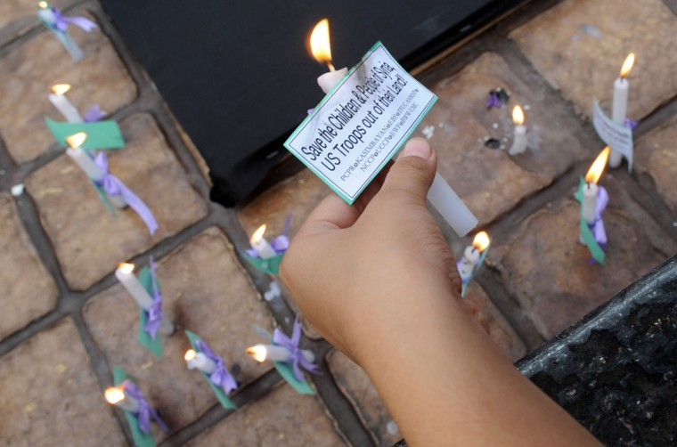 "Philippine protesters hold anti-U.S. placards and light candles during a prayer-vigil in Manila on September 7, 2013. The protesters said the U.S. should keep out of that country while presenting flowers and lighted candles in a ""peace sign for Syria."" (Jay Directo/AFP/Getty Images)"