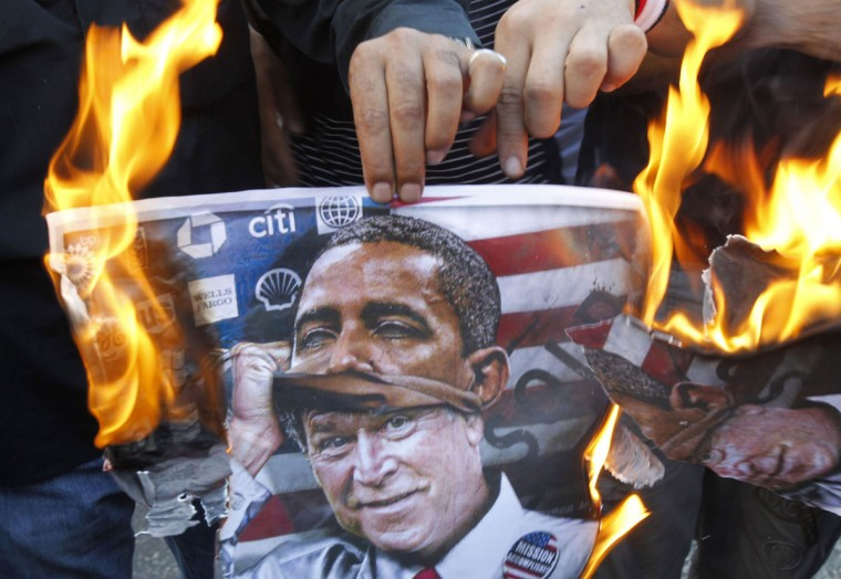 A protester holds a poster burning on which is depicted former U.S. president George W. Bush taking off a mask of current President Barack Obama during a demonstration of supporters of Syrian regime near the U.S. embassy, east of Beirut against a possible U.S. military strike on Syria on September 7, 2013. Obama is pressing Congress to approve military action against the Syrian regime in response to an alleged August 21 attack with chemical weapons. (Anwar Amro/AFP/Getty Images)
