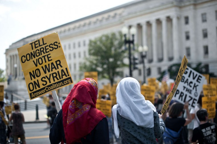 "A Syrian girl (left) and an Iranian girl hold signs outside the Rayburn House office building across from the .U.S Capitol in Washington during a demonstration against U.S. intervention in Syria on September 7, 2013. European Union foreign ministers on Saturday urged ""a clear and strong response"" to an alleged Syria chemical weapons attack while stopping short of endorsing a strike on the Damascus regime. Speaking after the bloc's 28 ministers held talks with US Secretary of State John Kerry, the EU's foreign policy chief Catherine Ashton read out a statement saying the ministers ""were unanimous in condemning in the strongest terms this horrific attack."" (Nicholas Kamm/AFP/Getty Images)"