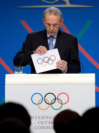 """IOC President Jacques Rogge prepares to show the card reading """"Tokyo"""" to announce the winner of the bid to host the 2020 Summer Olympic Games, during the 125th session of the International Olympic Committee (IOC), in Buenos Aires, on September 7, 2013. (Fabrice Coffrini/AFP/Getty Images)"""