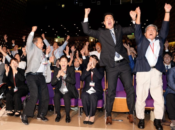 Japanese swimmers, Ai Shibata (front 3rd R) and Junichi Miyashita (front 2nd R), Japanese weight lifter Hiromi Miyake (front L), Japanese wrestler Saori Yoshidda (front 3rd L) and other participants celebrate after Tokyo was named for the 2020 Summer Olympics in Buenos Aires during the live streaming event in Tokyo on September 8, 2013. (Toshifumi Kitamura/AFP/Getty Images)