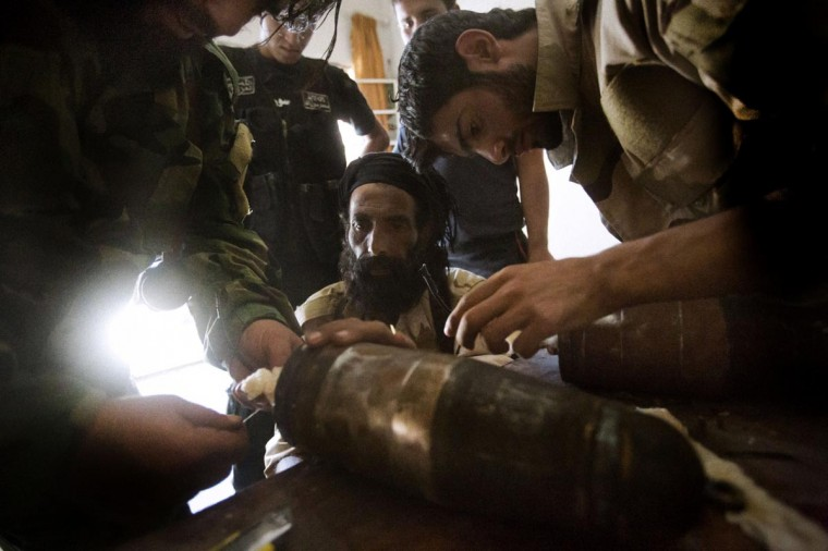 "Rebel fighters prepare explosive devices to be used during fighting against Syrian government forces on September 7, 2013 in Syria's eastern town of Deir Ezzor. The United States and France claimed growing international support for military strikes to punish the Syrian regime for an alleged chemical attack, after EU nations called for a ""strong response"". (Ricardo Garcia Vilanova/AFP/Getty Images)"
