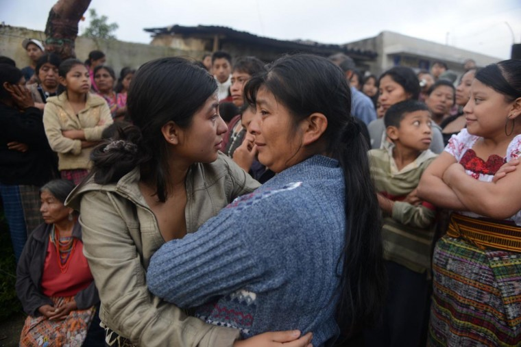 Women cry at a crime scene where eleven people were killed by alleged members of a gang in San Jose Nacauil municipality, 20 km north of Guatemala City, on September 8, 2013. Guatemala has been struggling with a wave of violence, related mainly to drug trafficking, that has seen an average of 16 people killed a day -- one of the highest murder rates in Latin America. (Johan Ordonez/AFP/Getty Images)