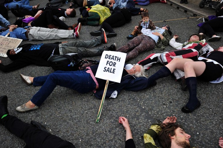 Protestors lie in the road during a demonstration against an arms fair at the ExCeL Centre in east London on September 8, 2013. (Carl Court/AFP/Getty Images)