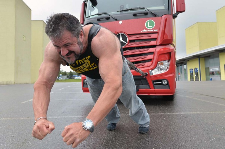 "Heinz Ollesch, for several times bearer of the title ""Strongest man of Germany"", pulls a seven-tons truck on September 9, 2013 in Chemnitz, eastern Germany, to promote the German Truck Pulling Championships. The competition is scheduled to take place during the Commcar fair for commercial cars from October 12 to 13, 2013 in Chemnitz. (Hendrik Schmidt/AFP)"