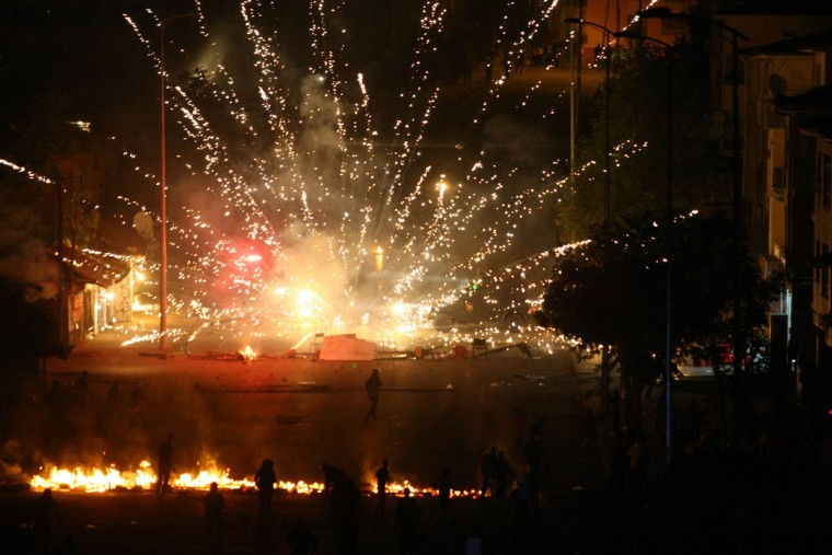 Turkish riot police are targeted with fireworks during a protest against a government project, the first ever cultural center containing an Alevi cemevi and a Sunni mosque side by side, in the Tuzlucayir neighborhood of Ankara, Turkey on September 12, 2013. (Adem Altan/AFP/Getty Images)