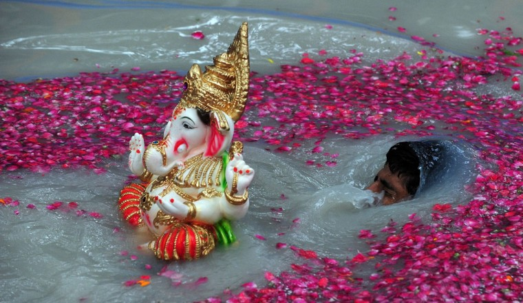 An Indian Hindu devotee carries an idol of elephant-headed Hindu god Ganesha for immersion inside an environmentally friendly artificial water tank on the fifth day of the ten-day long festival Ganesh Chaturthi, in Mumbai on September 13, 2013. Hindu devotees bring home idols of Lord Ganesha in order to invoke his blessings for wisdom and prosperity. The ten day Ganesh Festival sees millions of Hindus gathering along the western city's coast to immerse the elephant-god idols in the Arabian sea. (Indranil Mukherjee/AFP/Getty Images)