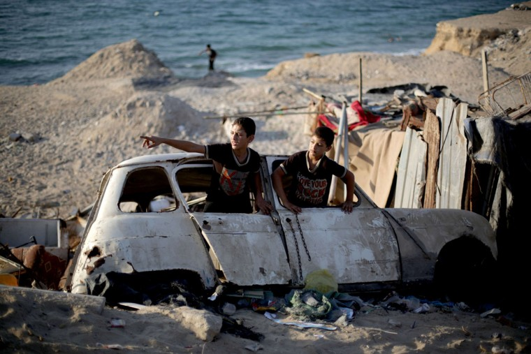 Palestinian children play in the wreckage of an old car in the Shati refugee camp in Gaza City on September 13, 2013. (Mohammed Abed/AFP/Getty Images)