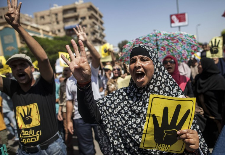 """Supporters of ousted Egyptian president Mohamed Mursi raise up posters with the four finger symbol during a demonstration against the military backed government in the Egyptian capital Cairo, on September 13, 2013. Thousands of Morsi supporters rallied in Cairo after Friday prayers chanting angry slogans against the military, with clashes reported elsewhere in Egypt. The four finger symbol, known as """"Rabaa"""", meaning four in Arabic, is used to remember those killed in the crackdown on the Rabaa al-Adawiya protest camp in Cairo earlier in the year. (Mahmoud Khaled/AFP/Getty Images)"""