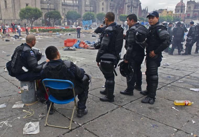 Mexican Federal Police officers rest at Mexico City's Zocalo Square after clashes with teachers protesting against an education reform. (Omar Torres / AFP/Getty Images)