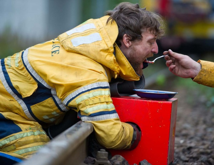 A Greenpeace activist spoon feeds an activist chained up to a rail track of a German division of Swedish energy giant Vattenfall in Welzow, eastern Germany, on September 16, 2013 to stage a protest against the company's planned brown coal mining. (Patrick Pleul/AFP)