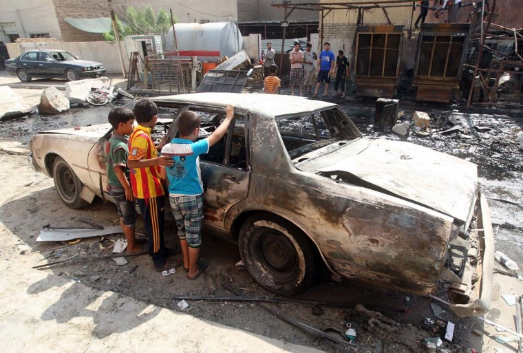 Iraqi children inspect a burnt-out car at the site of a car bomb attack that exploded the previous day in a commercial street of Baghdad's eastern neighbourhood of Mashtal on September 16, 2013. A wave of attacks across Iraq, the deadliest of which struck south of the capital, killed 26 people and left dozens more wounded, security and medical officials said. (Ahmad Al-Rubaye/AFP)