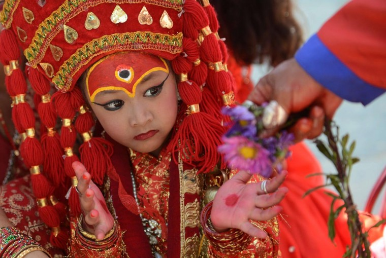 A young Nepalese girl dressed in the outfit of a Kumari, the living goddess, looks on as she takes part in Kumari Puja rituals at Hanuman Dhoka in Durbar Square of Kathmandu on September 17, 2013. (Prakash Mathema/AFP/Getty Images)