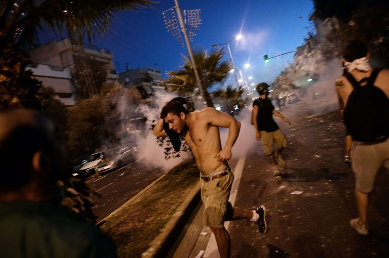 Protesters run away from police during clashes in the western Athens working-class suburb of Keratsini. (LOUISA GOULIAMAKI / AFP/Getty Images)