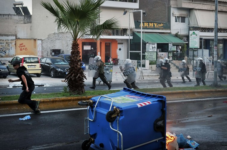 An anti-fascist protestor runs as riot police advance during clashes in Athens. (LOUISA GOULIAMAKI / AFP/Getty Images)