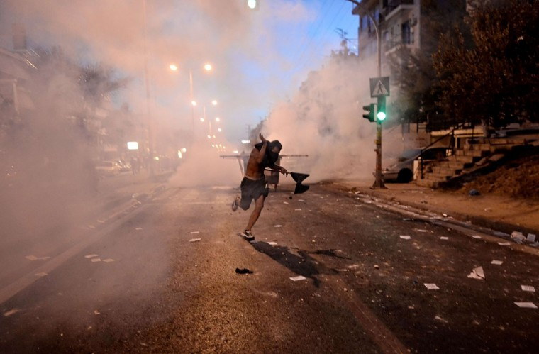 A demonstrator runs away from riot police during clashes in Athens after a leftist musician was murdered by a suspected neo-Nazi. (ARIS MESSINIS / AFP/Getty Images)