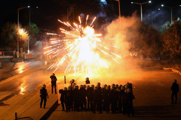 Turkish police stand in front of fireworks thrown by demonstrators during a protest on September 19, 2013 outside the Middle East Technical University (METU) in Ankara. (Adem Altana/AFP/Getty Images)