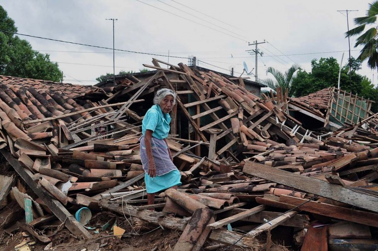 An old woman resident of a rural zone of Acapulco called Agua Caliente walks amid the rubble of of her home, in Guerrero state, Mexico on September 20, 2013. Mexico is reeling from the one-two punch of tropical storms Ingrid and Manuel, which have left a trail of destruction that damaged tens of thousands of homes, flooded towns and killed around 100 people. (Claudio Vargas/AFP)