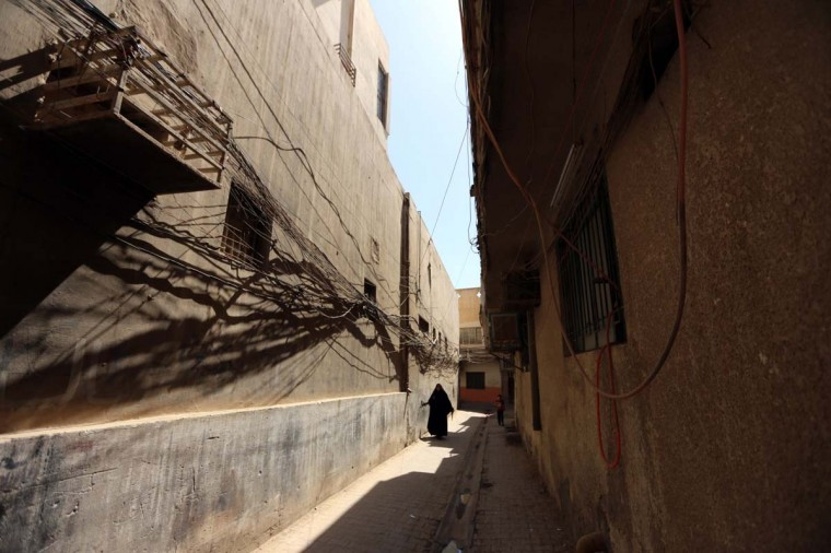 An Iraqi woman walks in a narrow street past electric cables hanged up on the walls on September 21, 2013 in the Iraqi capital Baghdad. Iraq is one of the world's leading oil producers, but its electrical infrastructure, heavily damaged during the war, is obsolete. (Sabah Arar/AFP