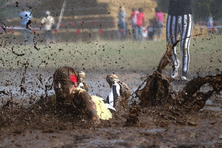 "A woman competes in ""The Mud day challenge"", a 13-kilometer obstacles course, on September 21, 2013 in Beynes near Paris, France. (Kenzo Tribouillard/AFP)"