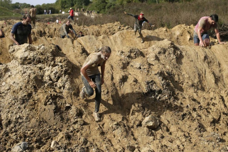 """Participants compete in """"The Mud day challenge"""", a 13-kilometer obstacles course, on September 21, 2013 in Beynes near Paris, France. (Kenzo Tribouillard/AFP)"""