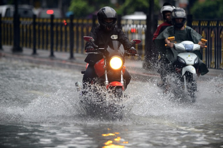 Motorists wade through flooded street in Manila. (NOEL CELIS / AFP/Getty Images)