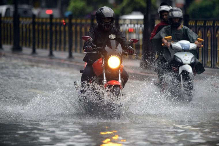 Motorists wade through flooded street in Manila. (NOEL CELIS / AFP/Getty Images)