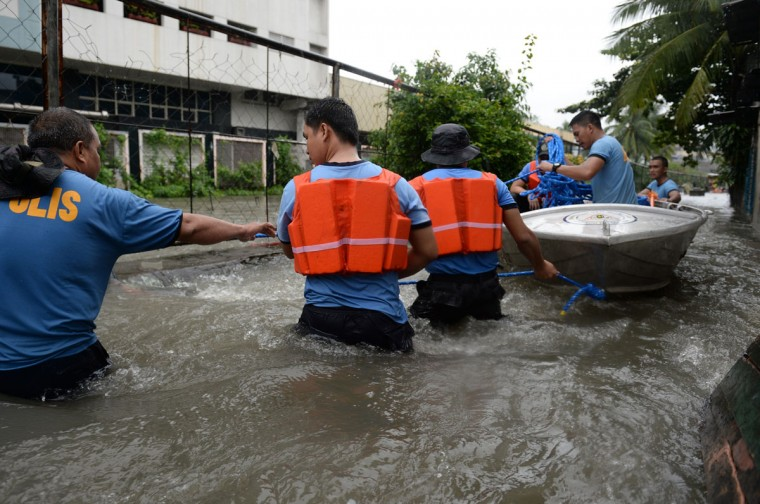 Rescuers pull a wooden boat through a strong current as they head for an informal settlers' area to rescue trapped residents from floodwaters along a street in Manila. )TED ALJIBE / AFP/Getty Images)