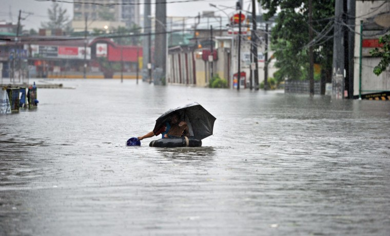 A resident using an innertube as a makeshift raft paddles through chest-deep floodwaters along a street in Manila. (TED ALJIBE / AFP/Getty Images)