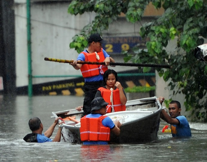 Rescuers pulling a wooden boat with a rescued resident on board wade through chest-deep floodwaters along a street in Manila. (TED ALJIBE / AFP/Getty Images)
