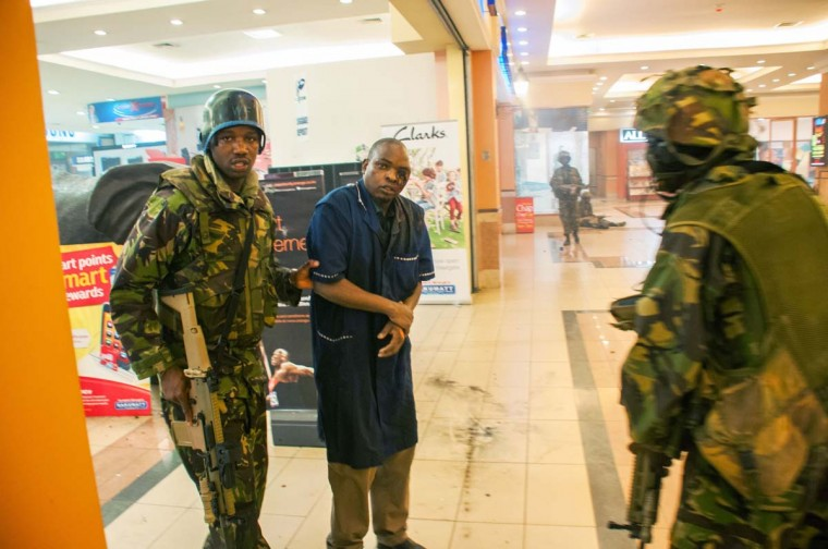 A severely wounded man is rescued by Kenyan troops at the Westgate Mall on September 21, 2013 in Nairobi. Kenyan troops were locked in a fierce firefight with Somali militants inside an upmarket Nairobi shopping mall on September 22 in a final push to end a siege that has left at least 59 dead and some 200 wounded with an unknown number of hostages still being held. Somalia's Al Qaeda-inspired Al-Shebab rebels said the carnage at the part Israeli-owned complex mall was in retaliation for Kenya's military intervention in Somalia, where African Union troops are battling the Islamists. (James Quest/AFP)