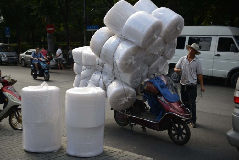 A salesman on a motorcycle unloads packing material for goods outside a market in Shanghai on September 23, 2013. China's manufacturing activity expanded in September to a six-month high, HSBC said on September 23, a further sign that a rebound in the world's second-largest economy is gaining momentum on improving demand. (Peter Parks/AFP)