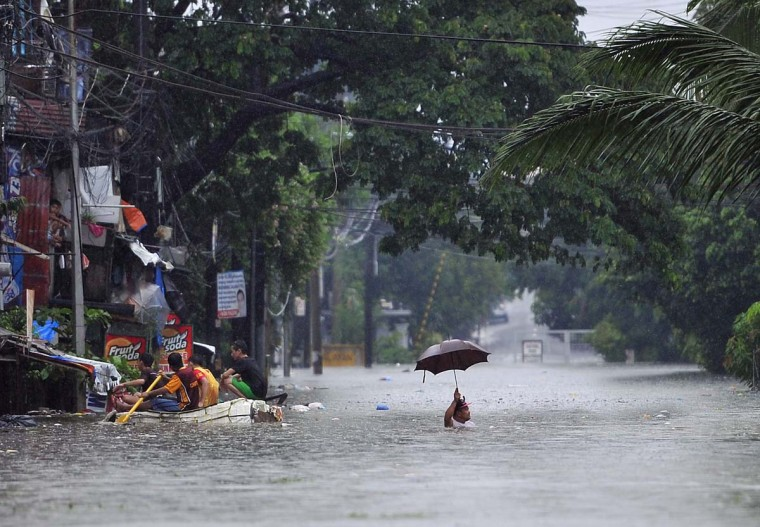 A resident (R) wades through chest-deep floodwaters along a street while his neighbours (L) paddle an improvised life raft in Manila on September 23, 2013, after torrential rains pounded Luzon island worsened by Typhoon Usagi. Monsoon rains worsened by Typhoon Usagi pounded the Philippines for the third day on September 23, causing floods and landslides that left six people dead and others stranded on rooftops, officials said. (Ted Aljibe/AFP)