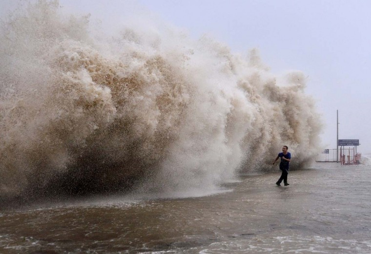 This photo taken on September 22, 2013 shows a man running away from a huge wave pushed up by Typhoon Usagi on a wharf in Shantou, south China's Guangdong province. Typhoon Usagi killed at least 25 people after crashing ashore in southern China, throwing the region's transport systems into chaos and leaving tens of thousands of airline passengers stranded in Hong Kong on September 23. (AFP)