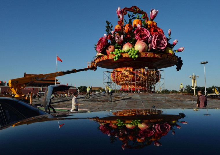 Workers install a giant vase containing fruit and flowers as part of China's upcoming National Day celebrations at Tiananmen Square in Beijing on September 24, 2013. The seven-day holiday sees millions of members of China's newly wealthy and mobile middle-class travel locally and abroad. (Mark Ralston/AFP/Getty Images)