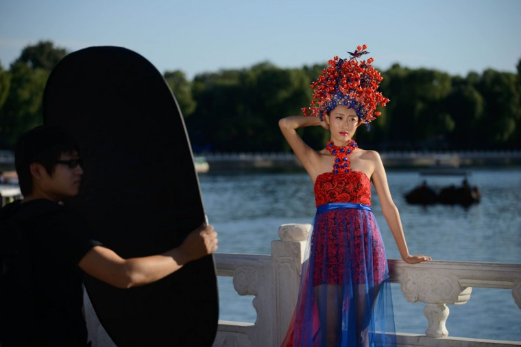 A model poses for a photographer beside a lake in a popular tourist area of Beijing on September 24, 2013. China's manufacturing activity expanded in September to a six-month high, a further sign that a rebound in the world's second-largest economy is gaining momentum on improving demand. (Ed Jones/AFP/Getty Images)